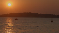 Beautiful sunset over the ocean with a fishing boat in the background Stock Footage