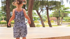 Little girl with hairtails in zebra dress walks roundabout park Stock Footage