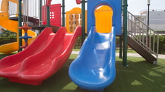 Little girl with hairtails climbs up slides down on playground Stock Footage