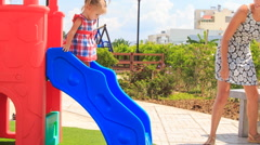 Little girl with hairtails tries slide down on playground Stock Footage