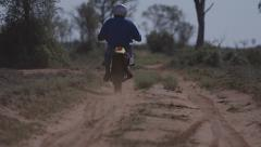 Motorbike rides away from camera long shot dusty Australian outback road Stock Footage