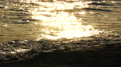Sea waves reflect glows on a sandy beach at sunset - soft slow motion Stock Footage