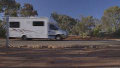Campervan RV caravan trailer drives dry red sandy creek bed in central Australia Stock Footage