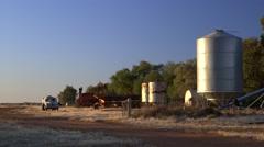 Farm equipment and grain silo on Australian outback farm at dawn, NSW Stock Footage