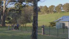 Outback house, woman brings garbage bin in, NSW, Australia Stock Footage