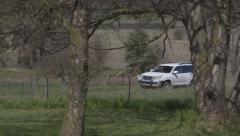 White 4WD car drives into farm along dirt road, pan left with vehicle - stock footage