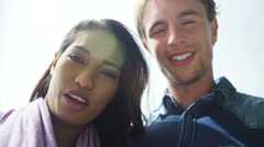 4K Romantic mixed ethnicity couple pose for a selfie in the city Stock Footage
