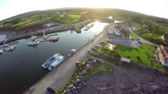 Stock Video Footage of Aerial view over fishing boats at dock at sunset in Gaspesie