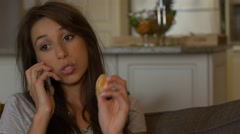 Attractive woman eats orange on couch while on phone Stock Footage