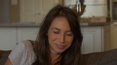 Attractive woman laughing on couch - close up Stock Footage