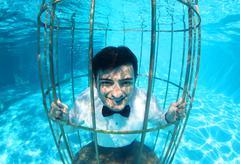 Funny groom underwater in a bird cage Stock Photos