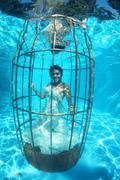 Fantasy bride underwater in a bird cage Stock Photos