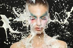 Fantasy makeup of beautiful girl with slow motion milk - stock photo