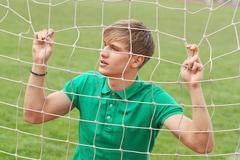 Young man looking through net soccer football goal catch Stock Photos