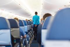 Interior of airplane with stewardess walking the aisle. Stock Photos