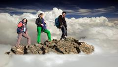 People walking on mountain ridge among clouds - stock photo