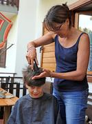 Stock Photo of Young mom cuts the hair of her son with the razor at home