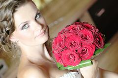 Beautiful woman bride makeup preparation with red flower bouquet - stock photo