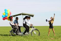 Stock Photo of baloons woman leading 4 guys on a quad bike on a green field sunny day