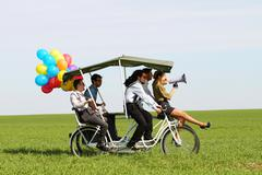 baloons woman leading 4 guys on a quad bike on a green field sunny day - stock photo