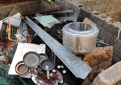 Old pans and washing machine basket in waste landfill Stock Photos
