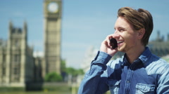 Stock Video Footage of 4K Portrait of attractive cheerful young man talking on mobile phone in London