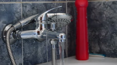 Shower faucet open expelling water in a bath Stock Footage