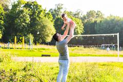 Baby girl walking in a summer park with her father Stock Photos