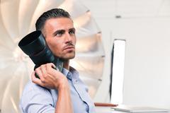 Thoughtful photographer holding camera Kuvituskuvat