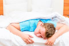sleeping man on a white bed sheets - stock photo