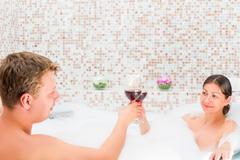 couple celebrates anniversary in the bath with foam - stock photo