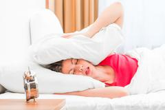 woman covering her ears pillows and fell asleep - stock photo