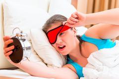 Awakened girl looks at an alarm clock with contempt Stock Photos