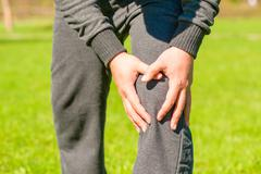 Male hands clasped sore knee outdoors Stock Photos