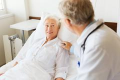 Stock Photo of doctor visiting senior woman at hospital ward