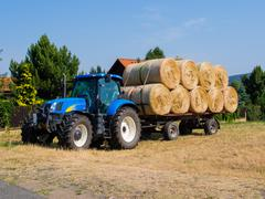 Tractor and wagon loaded with hay stacks during harvest time Stock Photos