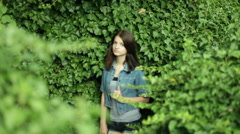 young dark-haired woman in the background of green plants - stock footage
