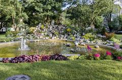 Group from small water fountains flowing in front beauty rockery - stock photo