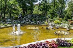 Group from small water fountains flowing in front beauty rockery Stock Photos