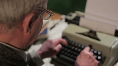 Old man is typing on a typewriter Stock Footage
