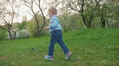 Happy little boy running in bloomy park Stock Footage