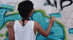 Teenage girl tagging wall with graffiti Stock Footage