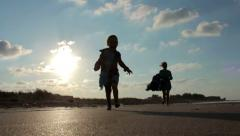 Silhouettes of Mother with her child running on the seashore, Slow Motion - stock footage