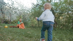 Mother and little son having happy time in bloomy garden Stock Footage