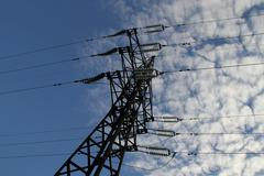 Pylon tower and wires of high voltage power line over cloudy sky - stock photo