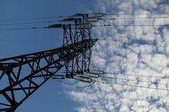 Pylon tower and wires of high voltage power line on blue sky background - stock photo