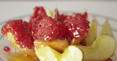 Honey poured on the pomegranate and apples. Jewishs new year Rosh Ha Shana. - stock footage
