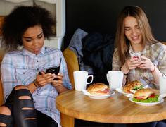 Multiracial girls with cell phones in a cafe Stock Photos