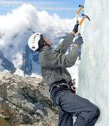 Man climbing on icefall in winter mountains Stock Photos