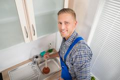 Young Happy Plumber Using Plunger In Kitchen Sink - stock photo